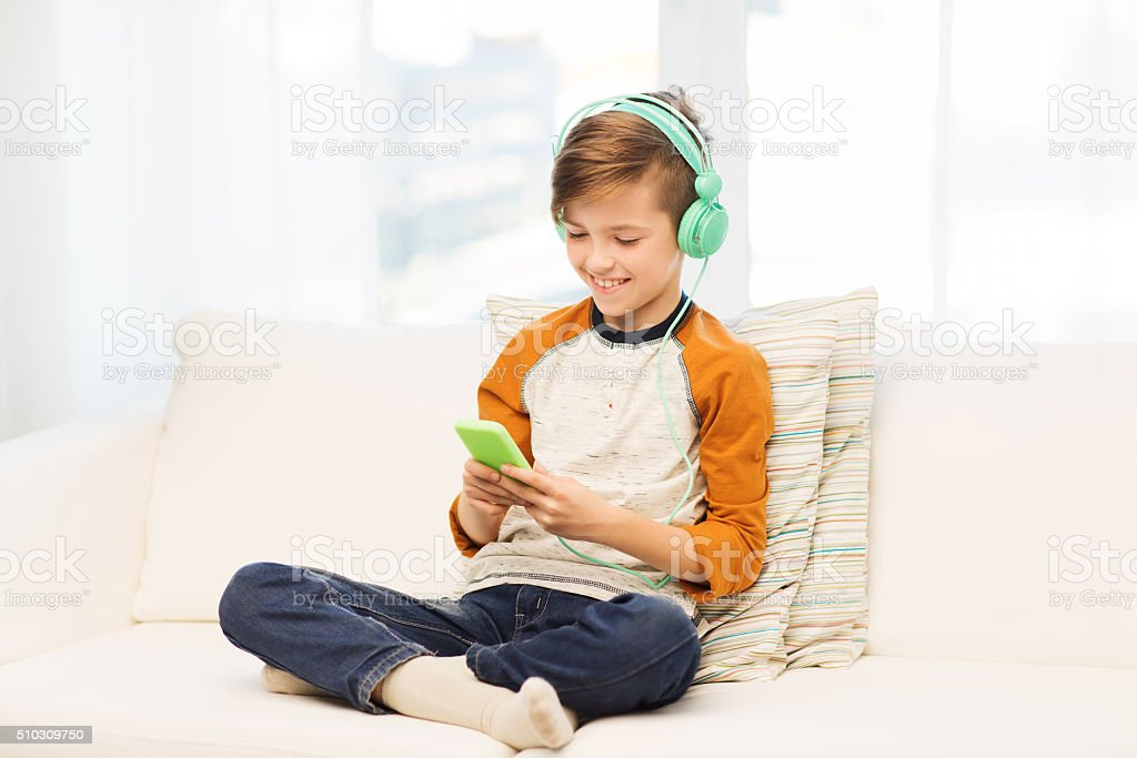 happy boy with smartphone and headphones at home stock photo