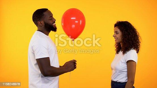 1125461272 istock photo Happy boyfriend giving red balloon to girlfriend on orange background, date 1158248978