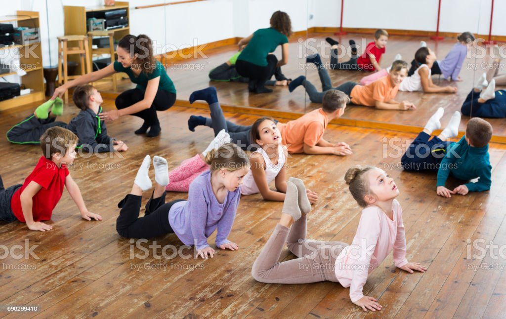 Happy boys and girls with trainer stretching in dance hall
