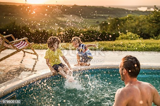 Small brothers having fun while their father is splashing them from the swimming pool.