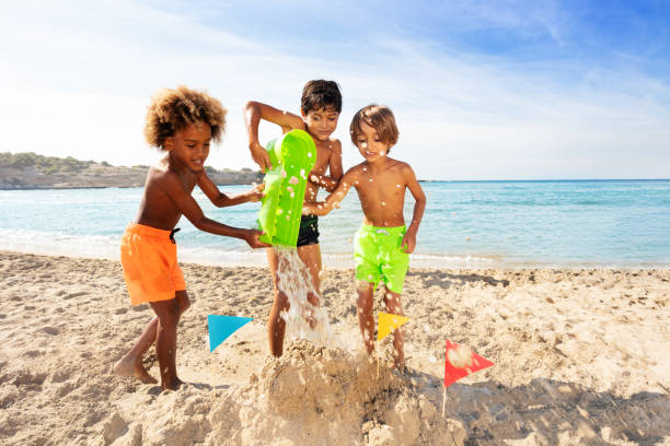 Happy Boys machen Sandburg zusammen am Strand – Foto