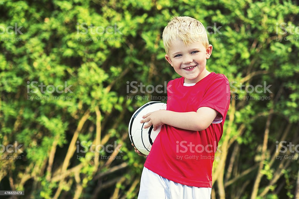 Happy boys smiles and holds a football royalty-free stock photo