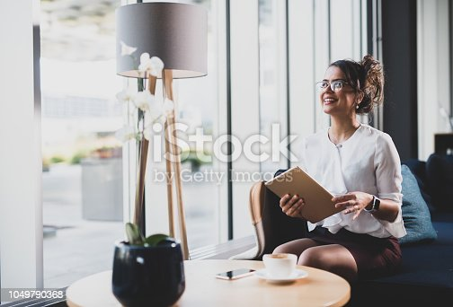 912944158istockphoto Happy Brazilian businesswoman holding iPad. 1049790368