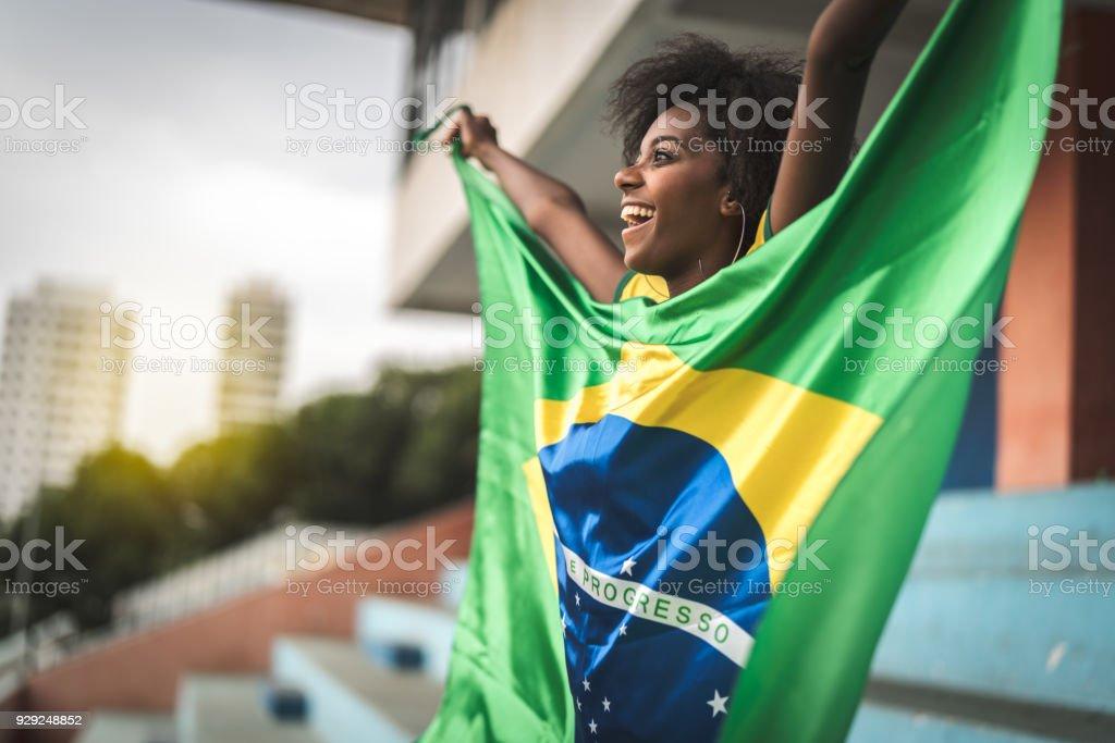 Happy Brazilian fan watching a soccer game stock photo
