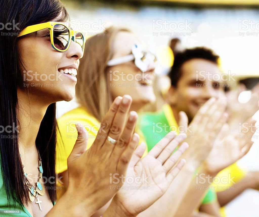 Happy Brazilian soccer fans clapping their team at a match stock photo