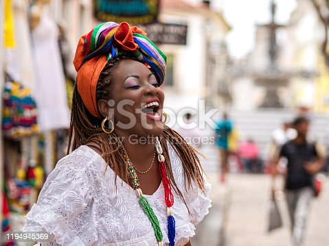 Happy Brazilian woman of African descent dressed in traditional Baiana costumes in the Historic Center of Salvador da Bahia, Brazil.