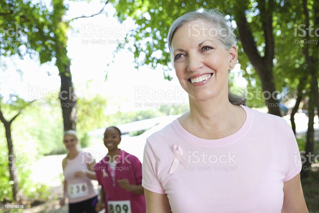 Happy breast cancer survivor completing charity race stock photo