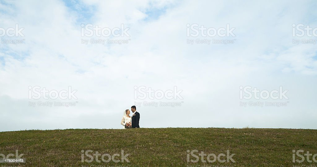 Happy bride and groom behind a grass hill stock photo