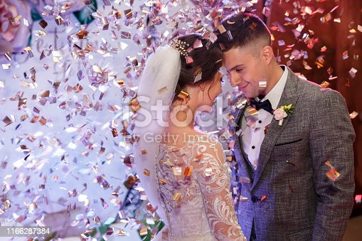 Happy bride and groom dancing under confetti at wedding reception. Wedding of beautiful caucasian couple, newlyweds dancing their first dance with special effects