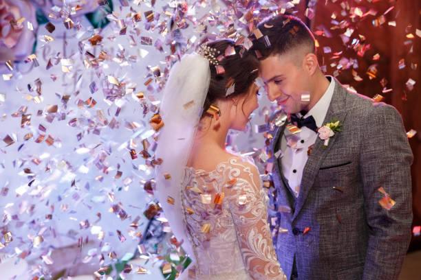 szczęśliwa narzeczeni tańczą pod konfetti na weselu. ślub pięknej kaukaskiej pary, nowożeńcy tańczą swój pierwszy taniec z efektami specjalnymi - panna młoda zdjęcia i obrazy z banku zdjęć