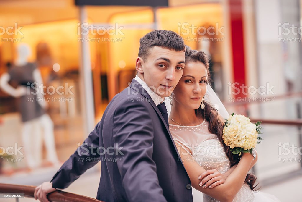 Happy bride and groom embracing in the shopping complex royalty-free stock photo