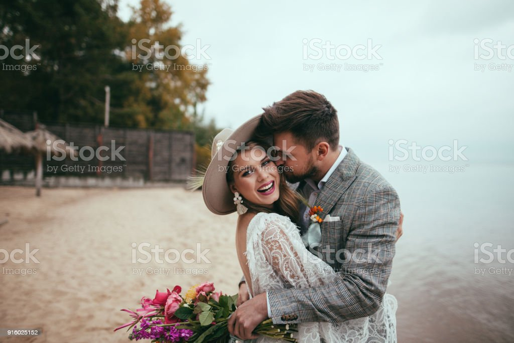 happy bride and groom in boho style embracing on beach stock photo
