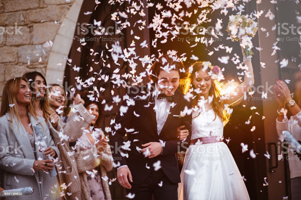 Happy bride and groom leaving church and celebrating stock photo