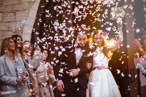 happy bride and groom leaving church and celebrating - wedding stock photos and pictures