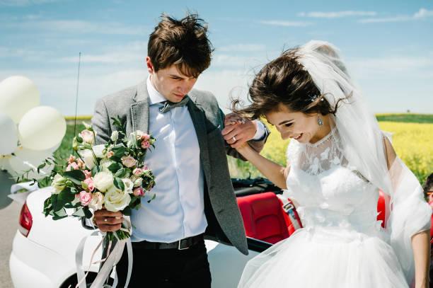 glückliche braut und bräutigam in der nähe des autos. der beste hochzeitstag und die ehe. gerade verheiratet. - hochzeitsfrisur boho stock-fotos und bilder