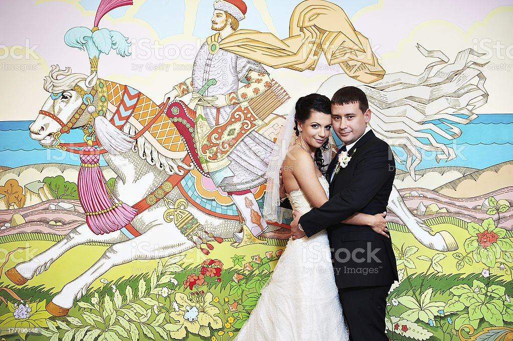 Happy bride and groom on background picture of fairy tales royalty-free stock photo