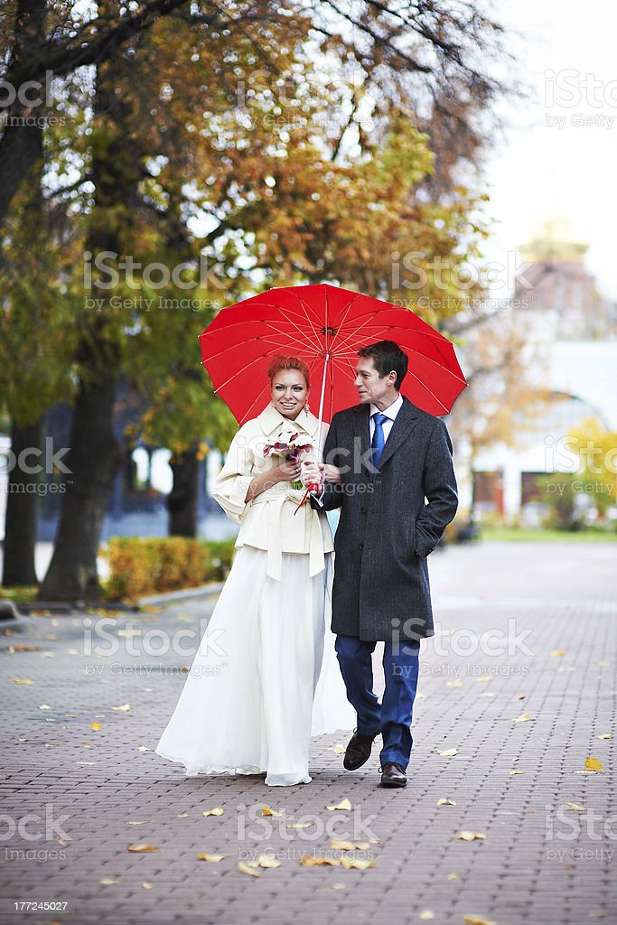 Happy bride and groom walking in yellow autumn park royalty-free stock photo