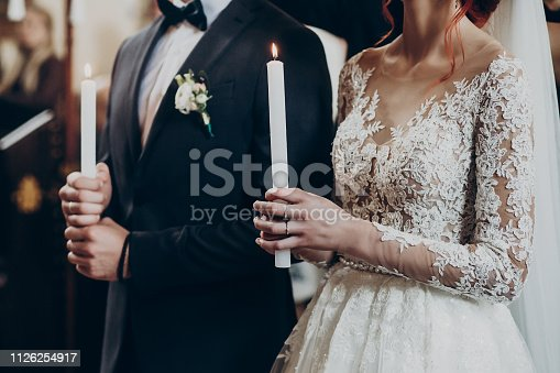 istock happy bride and stylish groom holding candles with light during wedding ceremony. wedding couple at matrimony in church. emotional moment, space for text. religion unity concept 1126254917