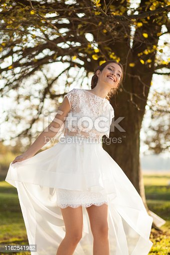 1054970060istockphoto Happy bride in nature 1162541982