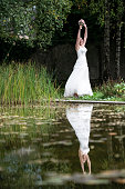 Happy bride jumping in the park with her hands up