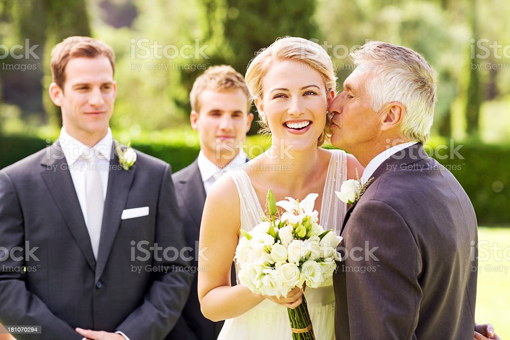Happy Bride Looking Away While Father Kissing Her On Cheek stock photo