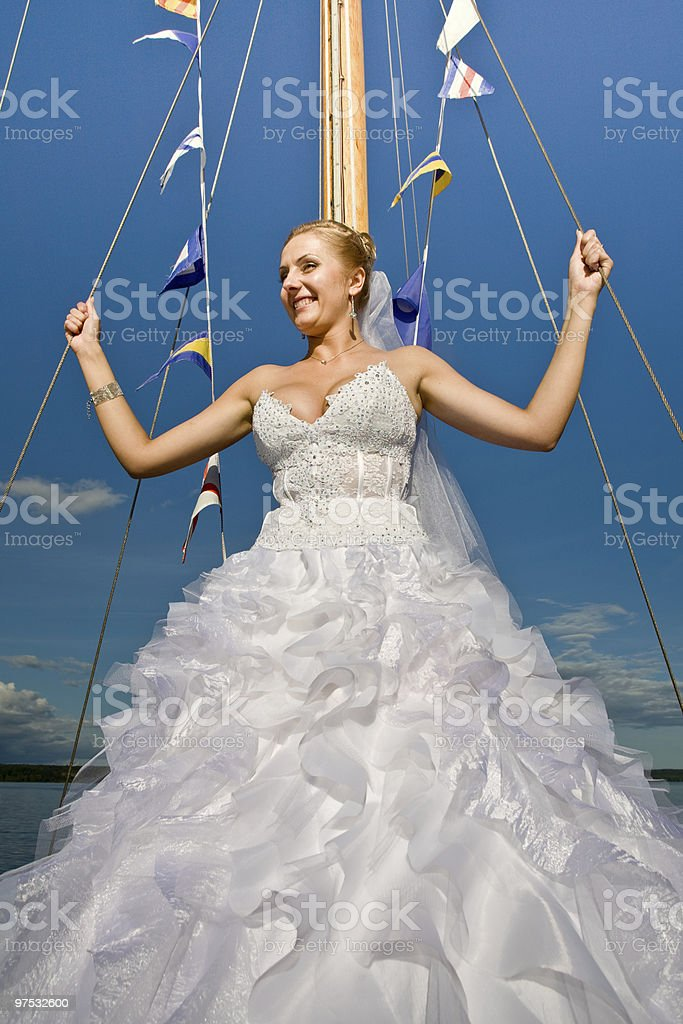 Happy bride posing at yacht mast agaisnt blue sky royalty-free stock photo