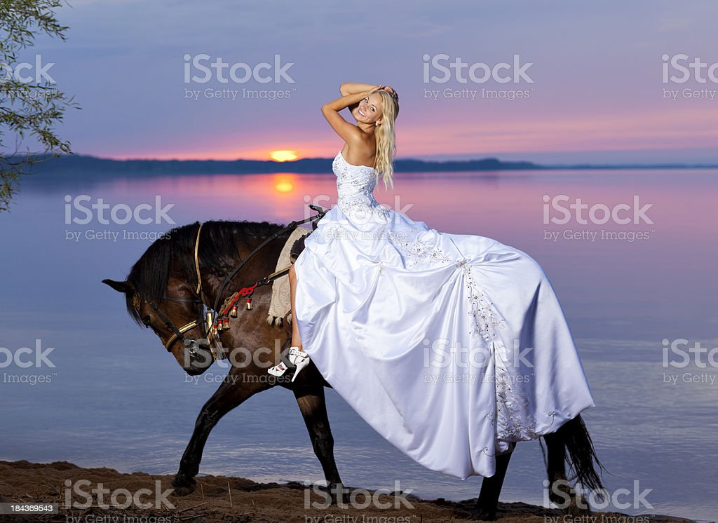 Happy bride riding a horse at sunset stock photo