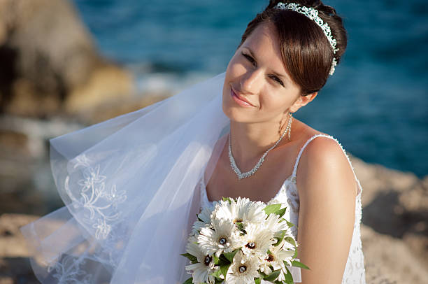 Happy bride with wedding bouquet on the sea. stock photo