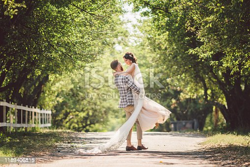 Happy bridegroom raises bride in summer park. man raised and hug woman to her arms. Newly wedded couple in the park. Just married. Walk in the park and hug. Newlyweds having fun. rustic wedding.