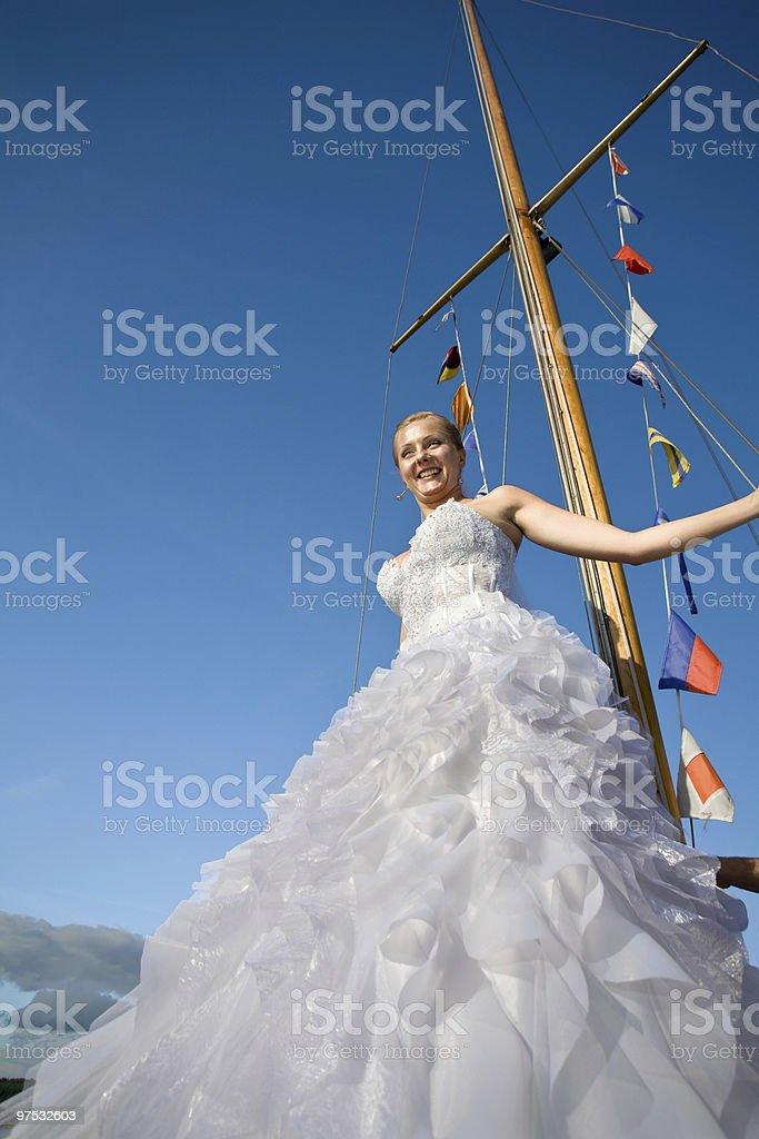 Happy brideposing at yacht mast agaisnt blue sky royalty-free stock photo