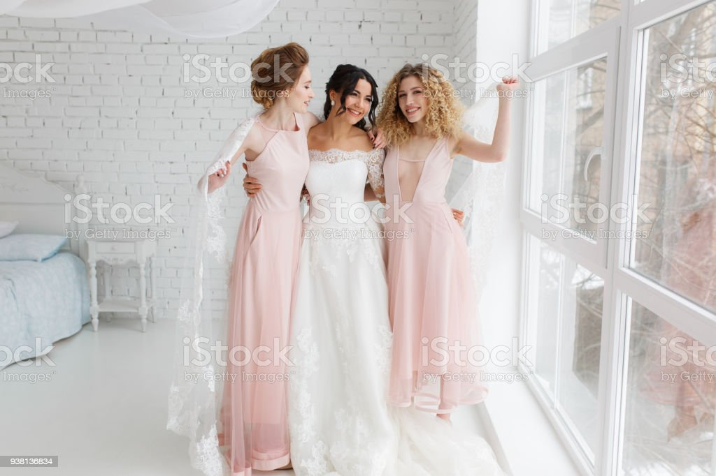 Happy bridesmaid hugging the bride in the bedroom in the morning stock photo