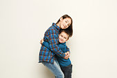 Portrait of happy hugging brother and sister, white studio background. Cute girl and boy embracing, smiling at camera, copy space