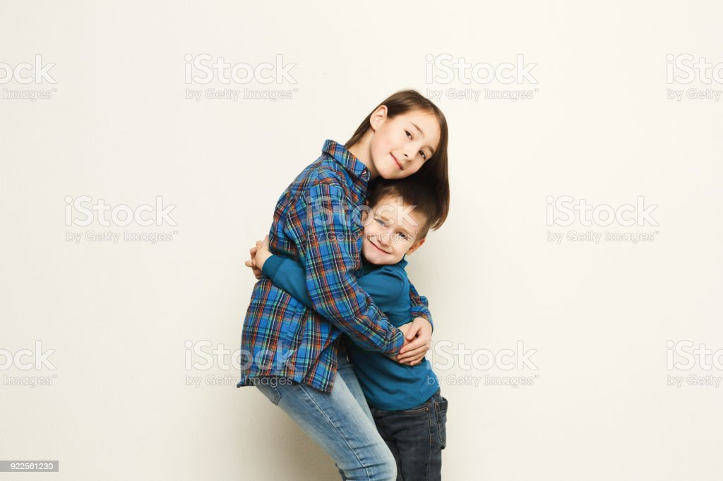 Happy brother and sister hug, studio background stock photo