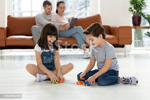 540396126 istock photo Happy brother and sister sitting on floor playing with toy. 1253390269