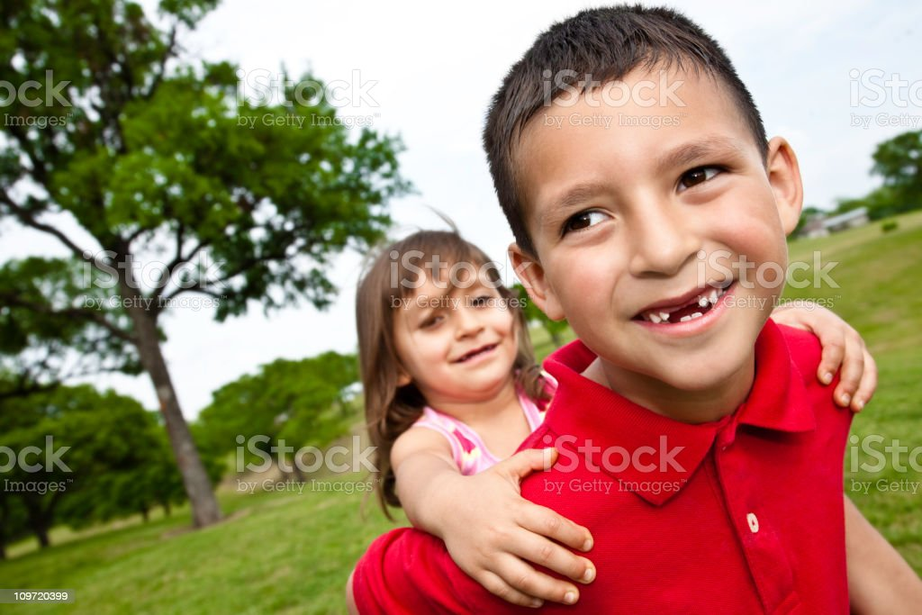 Happy Brother Giving Younger Sister Ride on Back at Park royalty-free stock photo