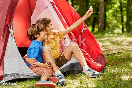 Happy brothers are taking selfie by tent. Smiling boys are camping in forest. They are spending leisure time.
