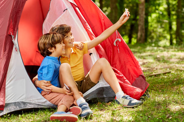 Happy brothers are taking selfie by tent in forest stock photo