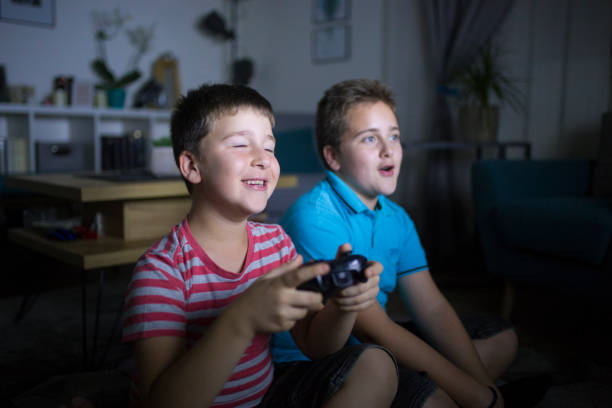 Happy brothers playing video games stock photo