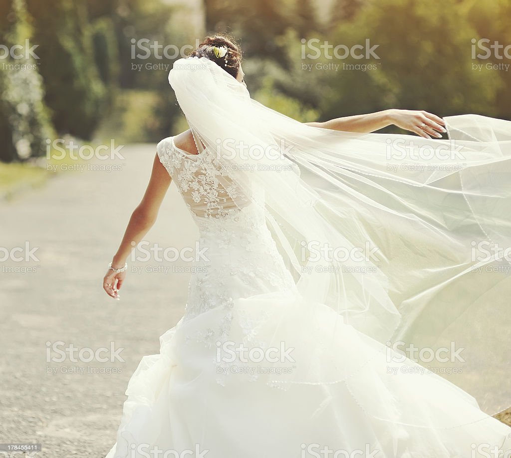 happy brunette bride spinning around with veil stock photo