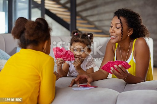 Playful mood. Young dark-skinned female keeping smile on her face while taking free card