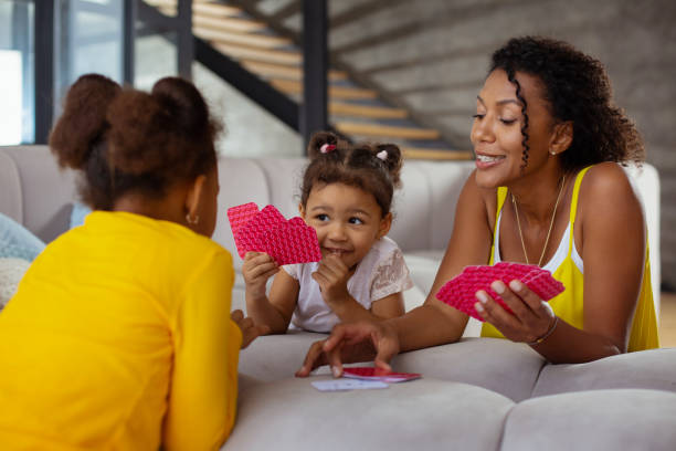 Happy brunette girl looking at her sister Playful mood. Young dark-skinned female keeping smile on her face while taking free card leisure games stock pictures, royalty-free photos & images