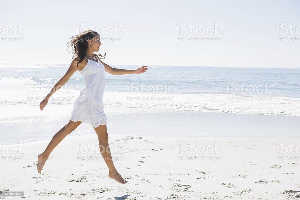 Happy brunette in white sun dress skipping on the sand stock photo