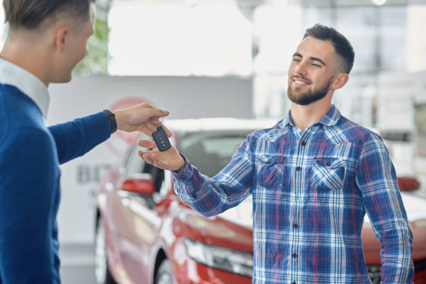 happy brunette man taking key from manager in car salon. - used car selling stock pictures, royalty-free photos & images
