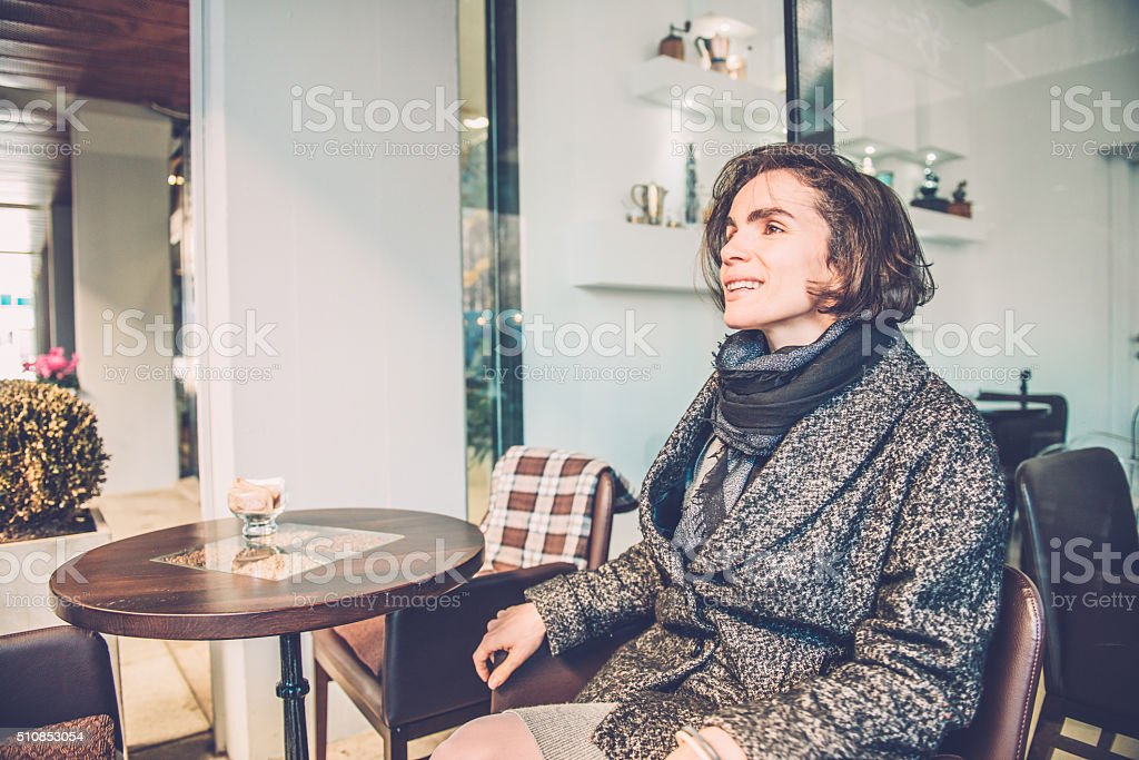 Happy Brunette Sitting in front of Caffe Trieste, Europe stock photo