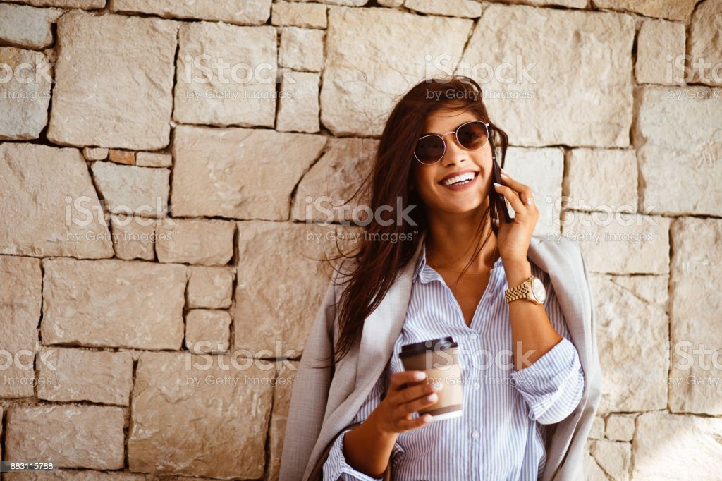 Happy brunette woman drinking coffee and talking on the phone stock photo