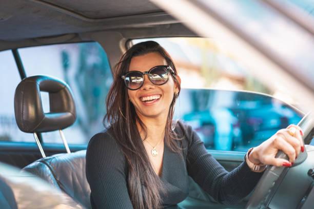 mulher triguenha feliz que conduz um carro - carro mulher - fotografias e filmes do acervo