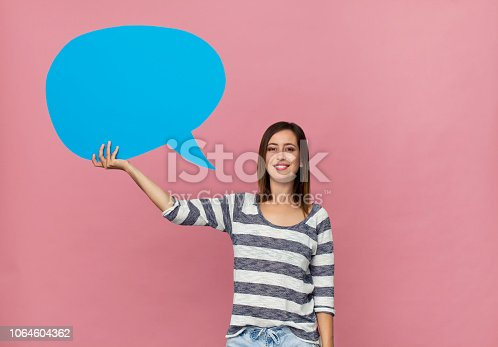 465462550istockphoto Happy brunette woman in casual clothes with blue speech bubble on pink background 1064604362