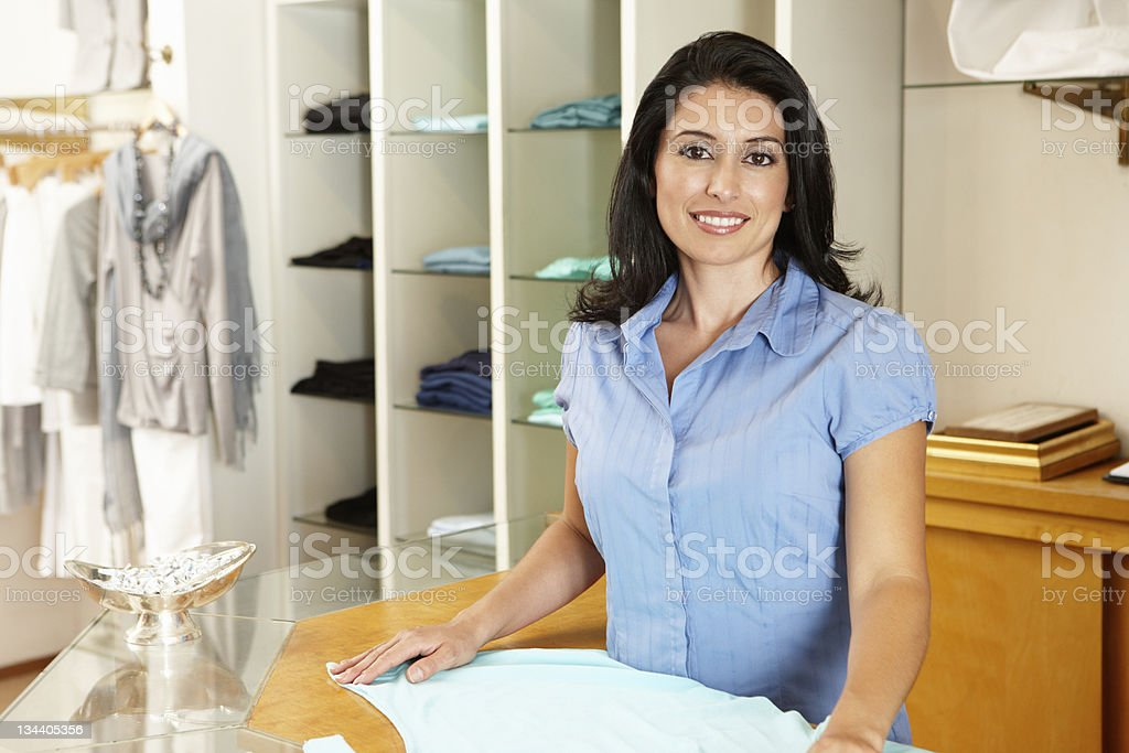 Happy brunette woman working in a woman's fashion boutique royalty-free stock photo