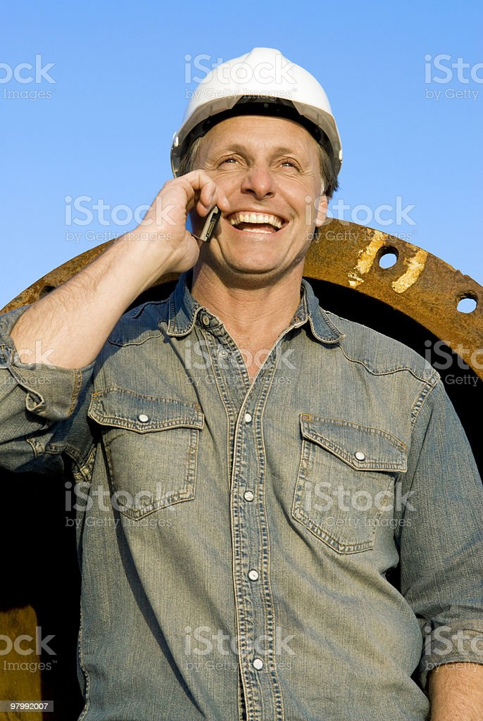 happy builder on cellphone. royalty-free stock photo
