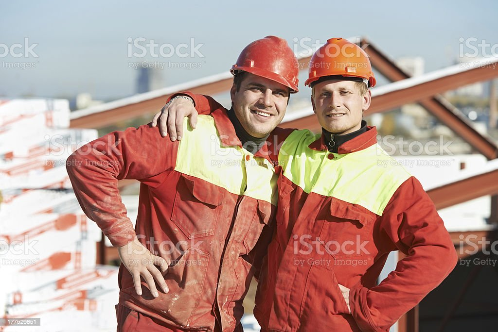 happy builder workers at construction site royalty-free stock photo
